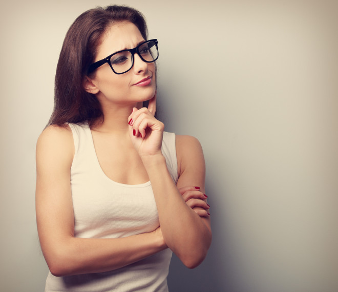 Thinking serious young woman in glasses looking. Vintage closeup