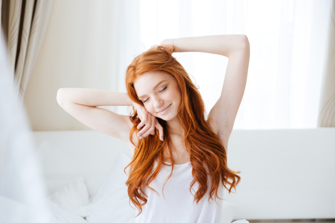 Sensual smiling woman sitting and stretching in bed