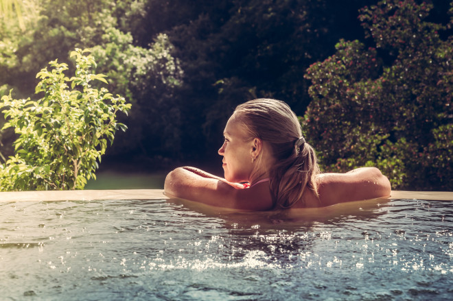 Woman relaxing in hotel  swimming pool looking at view