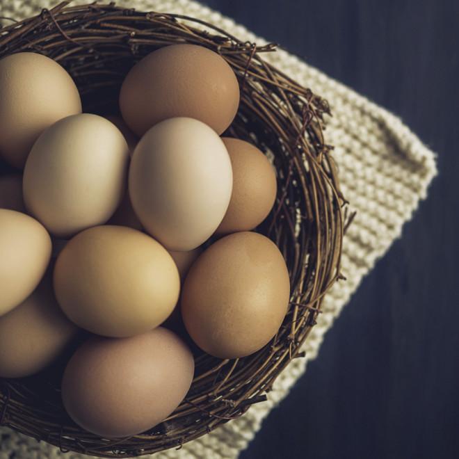 Fresh organic free range eggs in bowls with towel