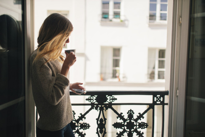 Woman drinking coffee at the balcony