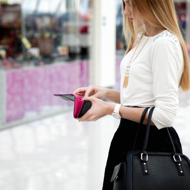 Young female in fashionable clothes looking into a wallet