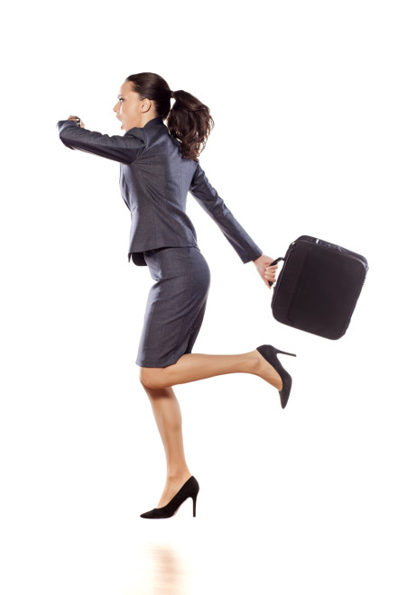 Excited business woman running and looking at her watch