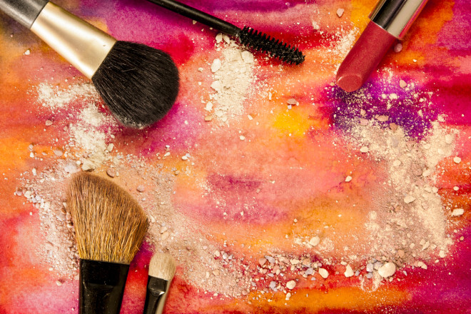 Makeup brushes and lipstick on vibrant painted background