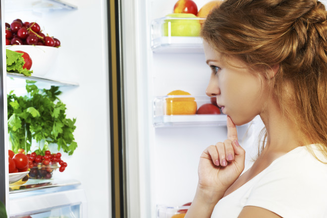 Happy woman and open refrigerator with fruits, vegetables