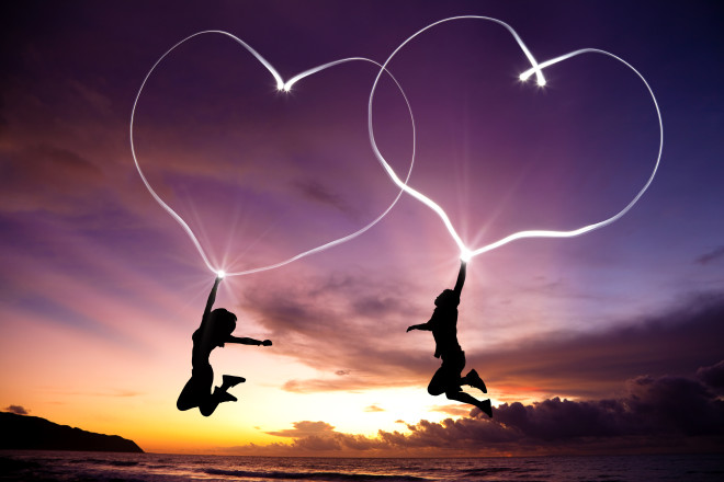 young couple jumping and drawing connected hearts by flashlight