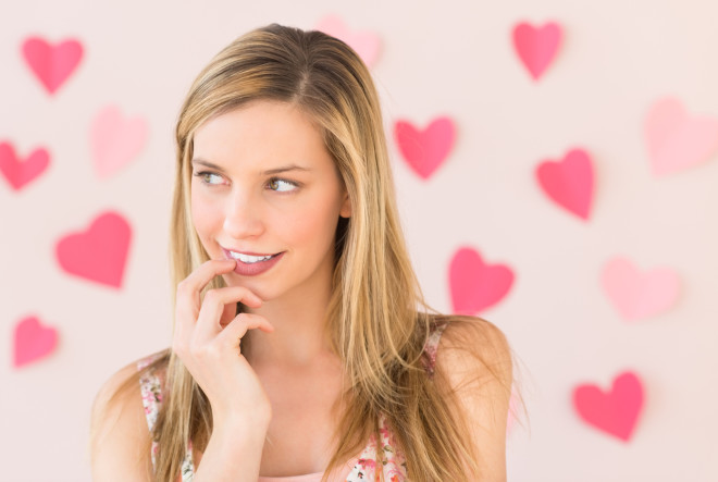Thoughtful Woman With Heart Shaped Papers Against Colored Backgr