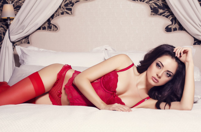 sexy brunette in red lingerie lying in the bed