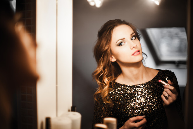 Brunette woman with blue eyes looking herself in the mirror