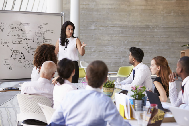 Hispanic Businesswoman Leading Meeting At Boardroom Table