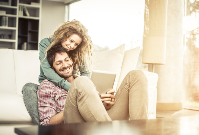 Couple looking tablet at home