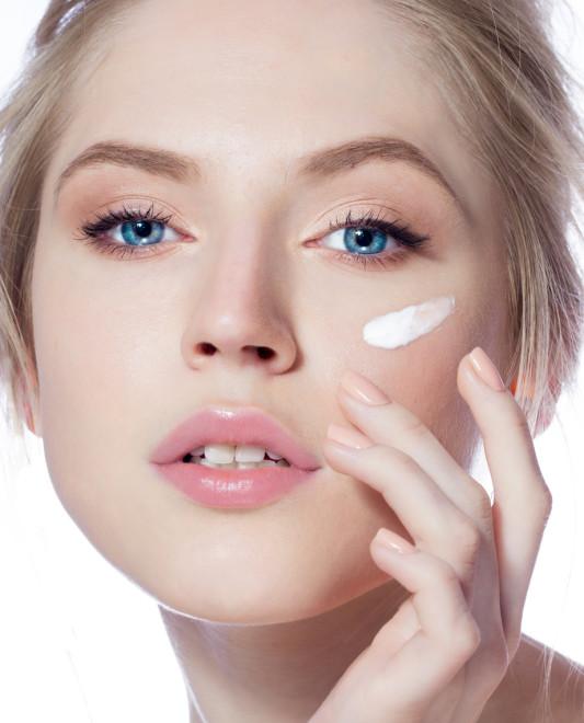 Portrait of young woman applying moisturizer cream
