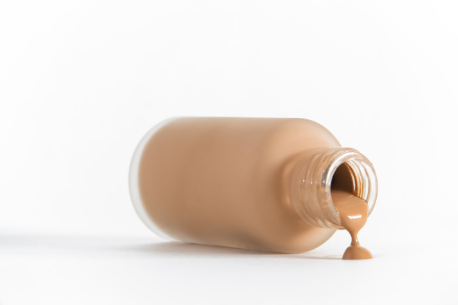 Isolated image of bottle of make-up on its side pouring out