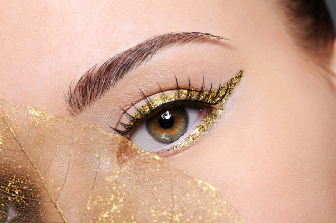 Female eye with a golden arrow make-up
