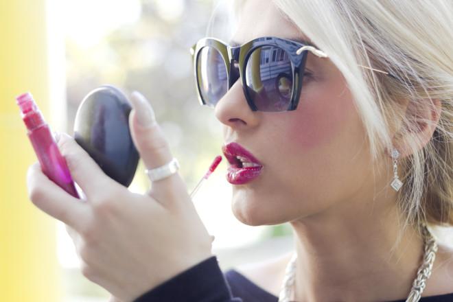 Beautiful blonde girl applying lip gloss over red lipstick