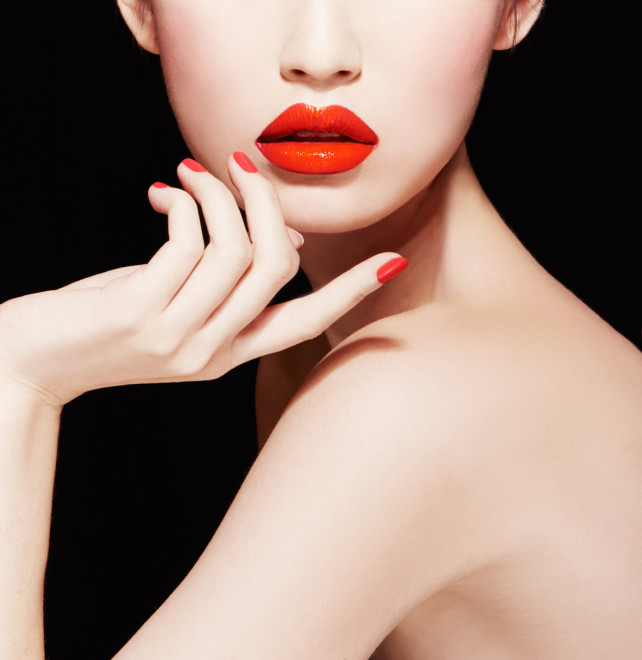 Beautiful makeup. red lips, nail polish manicure.isolated on black.