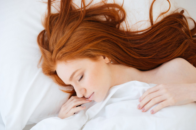 Tender woman with red hair sleeping in bed