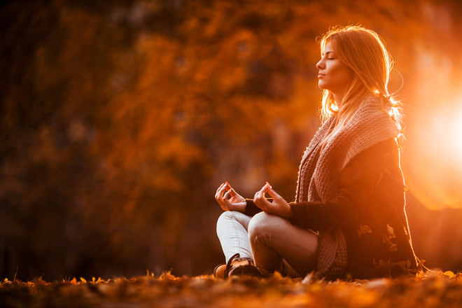 Woman meditating in autumn day.