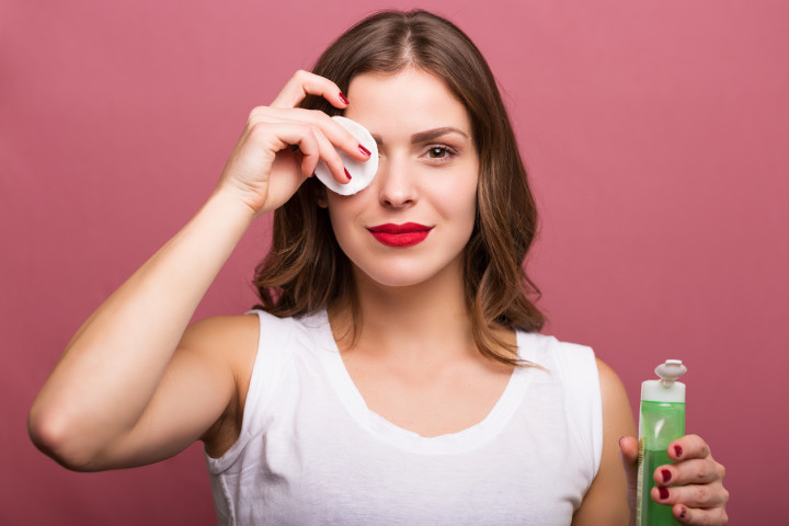Woman holding a lotion and a cotton pad