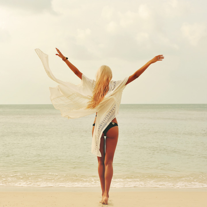 Woman enjoying nature at the beach. Arms wide open, freedom