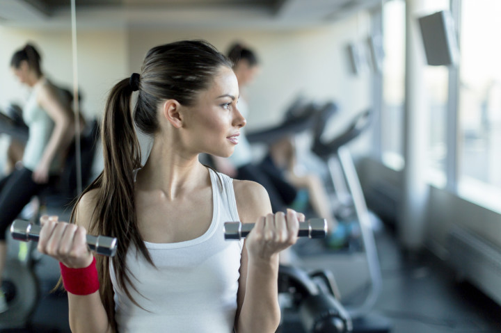 Beautiful, young woman lifting weights in a gym