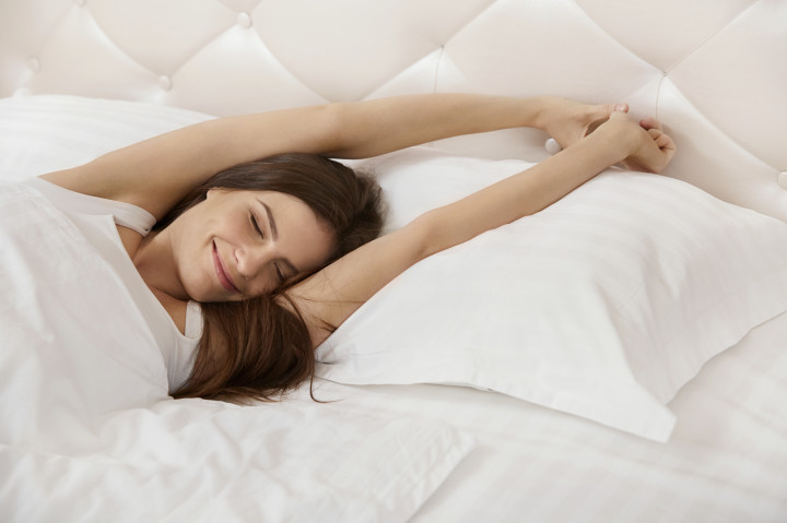 Woman stretching in bed. Girl Waking Up in The Morning
