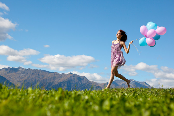 Woman wearing dress and running with balloons