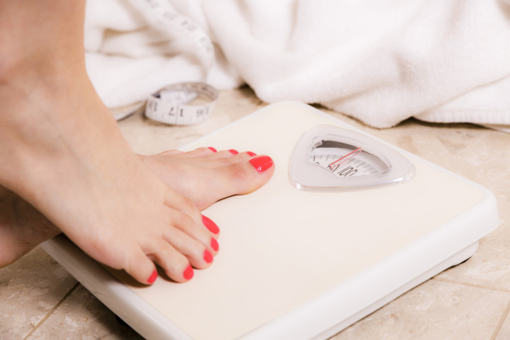 Healthy Lifestyle:  Weight conscious woman steps on bathroom scale.