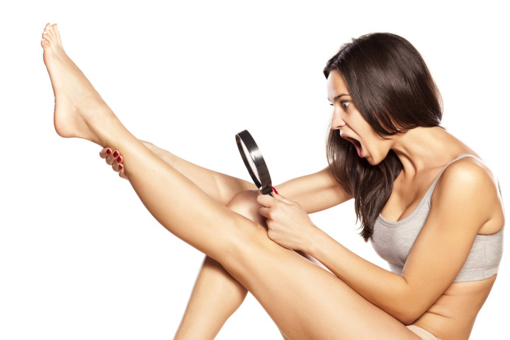 Disgusted girl looking at hair on her legs