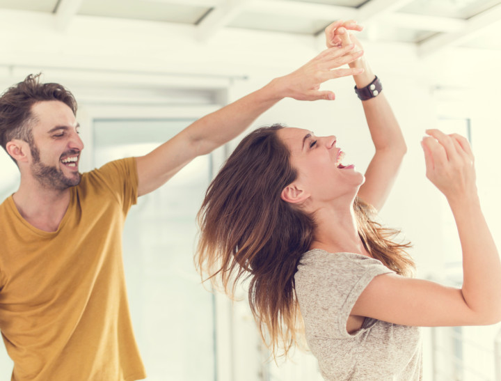 Cheerful couple having fun while dancing together.