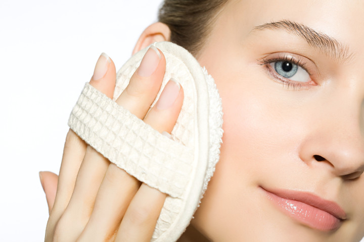 Young woman exfoliating face