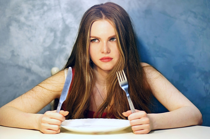 Hungry young woman waiting with an empty plate