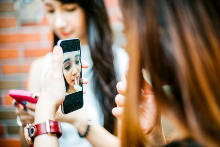 Japanese Teenage Girls using Smartphone as Vanity Mirror