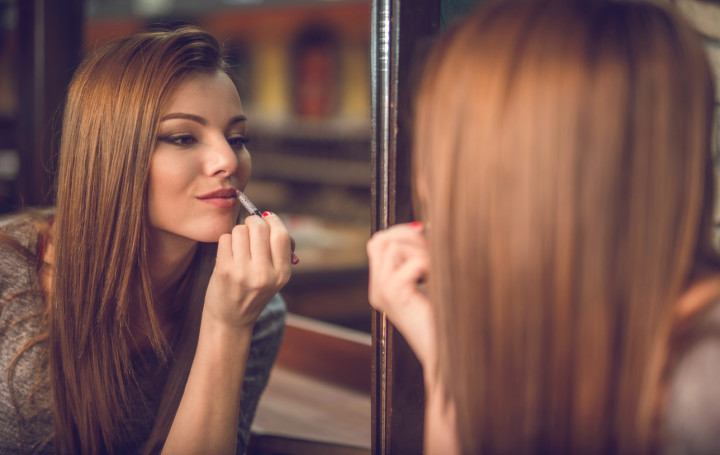 Reflection in mirror of a beautiful woman applying lipstick.