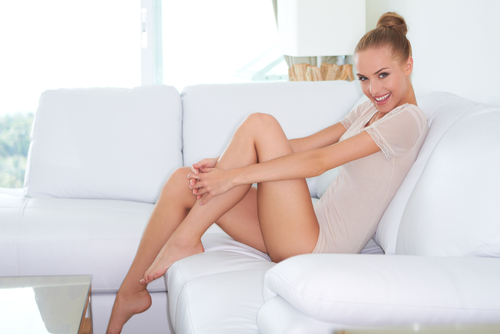 beautiful woman sitting on a white sofa with her bare feet up