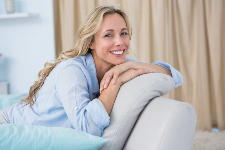 Cheerful pretty blonde sitting on couch at home
