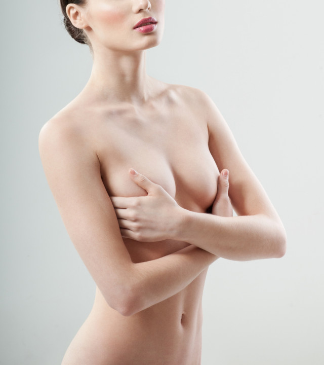 Beautiful woman covering her nude breast