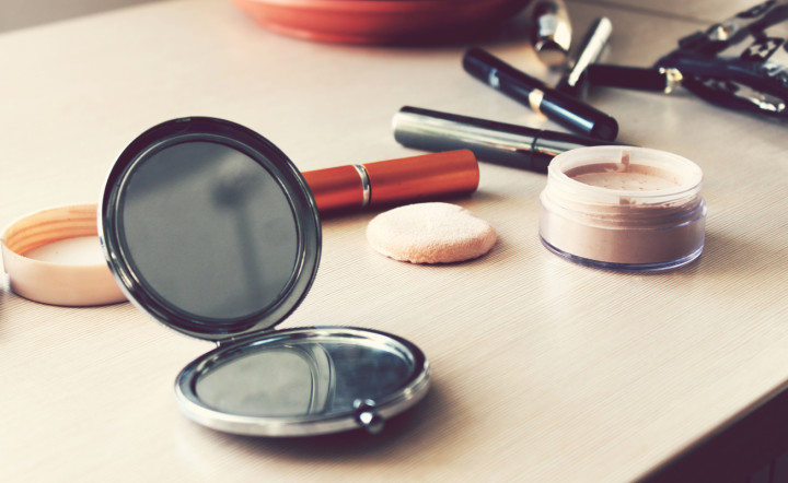 Mirror, powder, puff, eyeliner and other cosmetics on the table