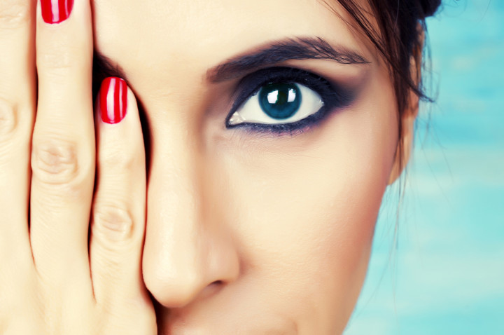 Young woman with make up on covering one eye
